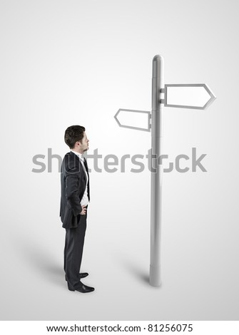 Businessman standing at a crossroad. A signpost points at multiple directions