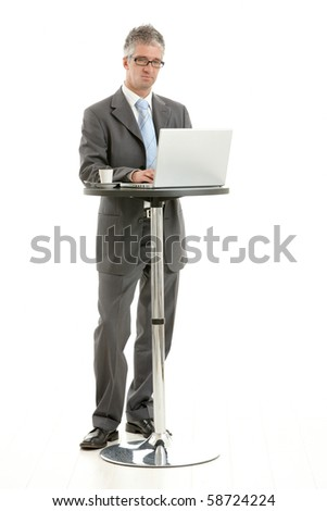 Businessman standing at coffee table, using laptop computer, looking at screen. Isolated on white.