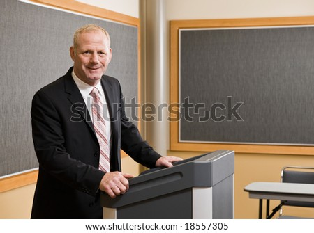 Businessman standing behind podium preparing to give presentation in conference room