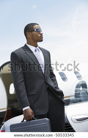 stock-photo-businessman-standing-beside-airplane-hand-in-pocket-holding-a-briefcase-50533345.jpg