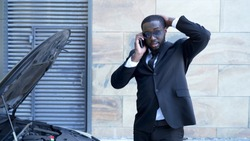 Businessman standing by broken car with open hood, talking over phone, breakdown