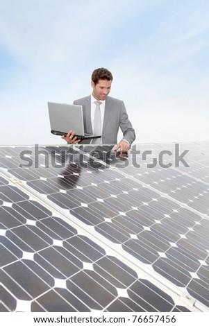 Businessman standing by solar panels