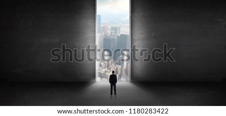 Businessman standing in a dark room and looking outside to a cityscape view #1180283422