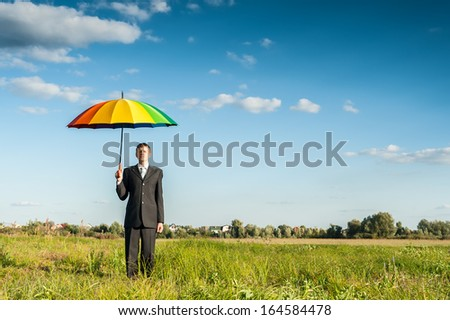 Businessman standing in a green field with multicolored umbrella.