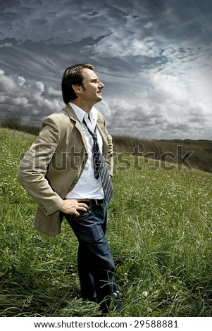 businessman standing in  a meadow with dark clouds behind