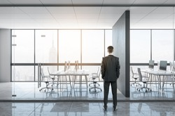 Businessman standing in bright office interior. Boss and executive concept.