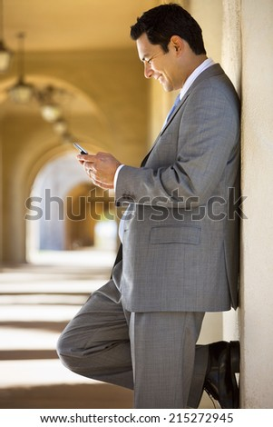 Businessman standing in building arcade, looking at text message on mobile phone, smiling, profile