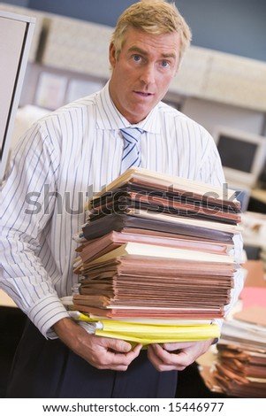 Businessman standing in cubicle with stacks of files - stock photo