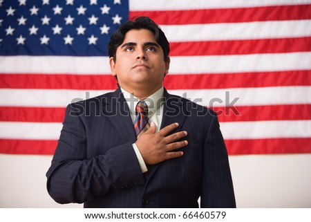 Businessman standing in front of an American flag with one hand across his heart
