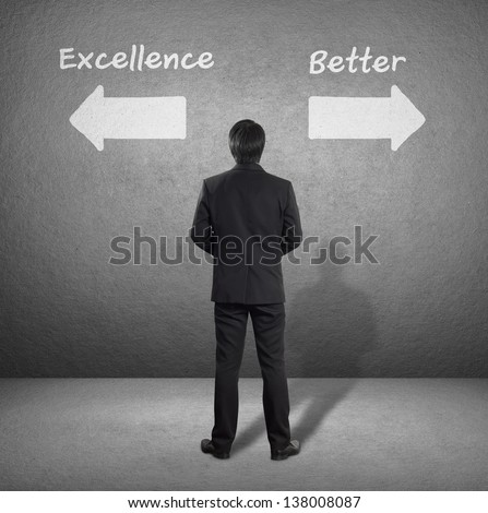 businessman standing in front of two arrows showing two different directions between Excellence or Better