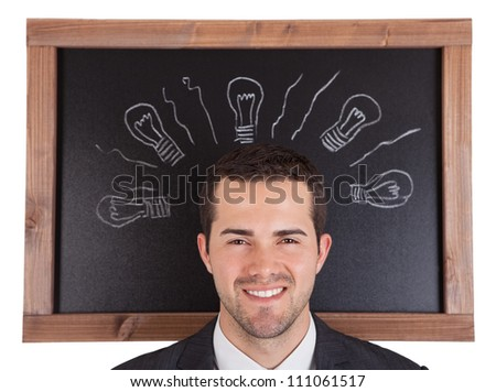 Businessman standing in front on blackboard. Isolated on white