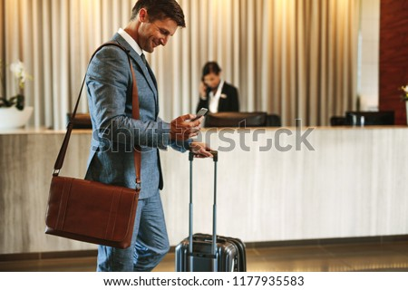 Businessman standing in hotel lobby with suitcase and using his mobile phone. Male business traveler in hotel hallway with smartphone and luggage.
