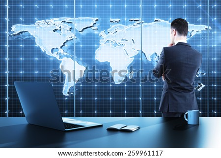 businessman standing in modern office and looking to global business map