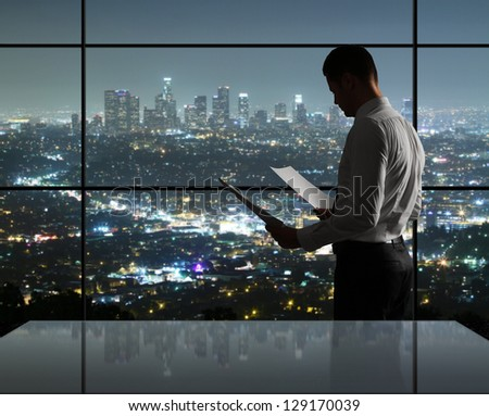 businessman standing in night office