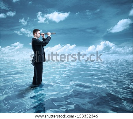 businessman standing in ocean and  looking through a telescope