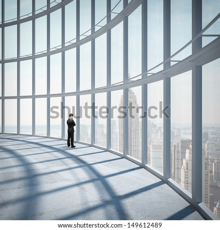 businessman standing in office and looking at city in window