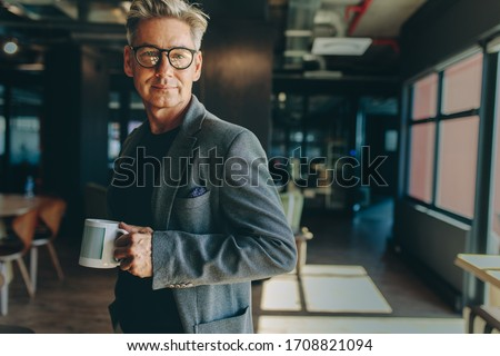 Businessman standing in office holding a coffee cup. Entrepreneur having a coffee break in office looking at camera.