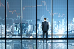 Businessman standing in office interior with glowing forex chart hologram. Trade and stats concept. Double exposure