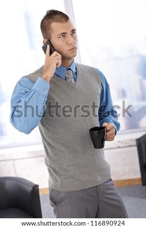 Businessman standing in office with coffee cup handheld, listening to mobile phone conversation, concentrating.