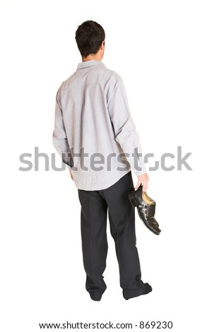 Businessman standing in socks, holding shoes in one hand.