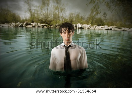 Businessman standing in the middle of water