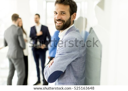 Businessman standing in the office and other business people talking at background #525163648