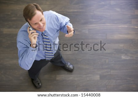 Businessman standing indoors using cellular phone and smiling