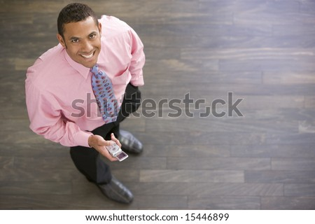 Businessman standing indoors with cellular phone smiling