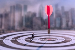 Businessman standing lookup red dart arrow hitting target centre dartboard on blurred cityscape background. Business targeting and focus.