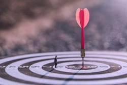 Businessman standing lookup red dart arrow hitting target centre dartboard on sunset background. Business targeting and focus.