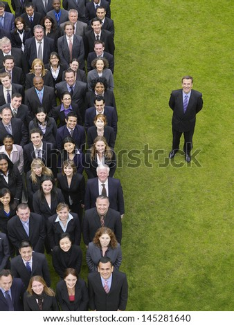 Businessman standing next to large group of multiethnic businesspeople in row