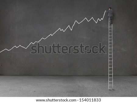 Businessman standing on a giant ladder and writing a chart