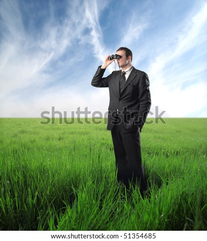 Businessman standing on a green meadow and using binoculars