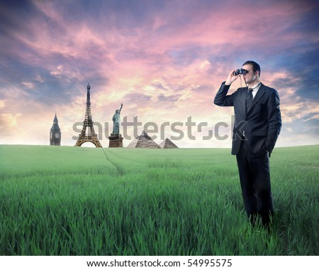 Businessman standing on a green meadow and using binoculars with landmarks from different cities on the background