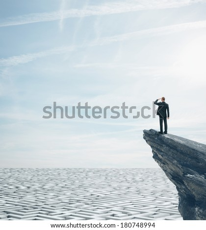Businessman standing on a rock and looking at huge labyrinth