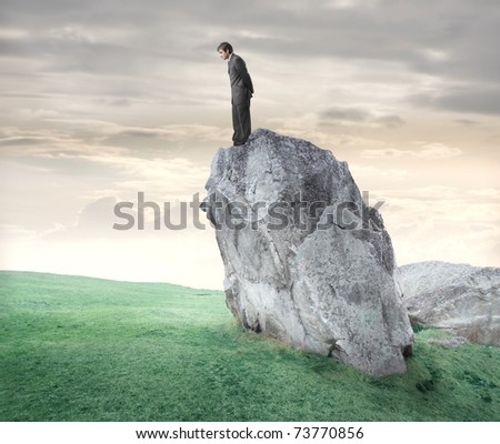 Businessman standing on a rock and looking downwards