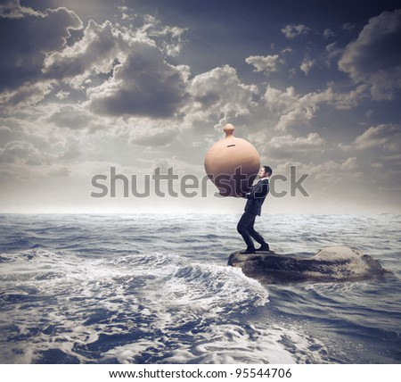 Businessman standing on a rock in the middle of a slight sea and holding a giant money box