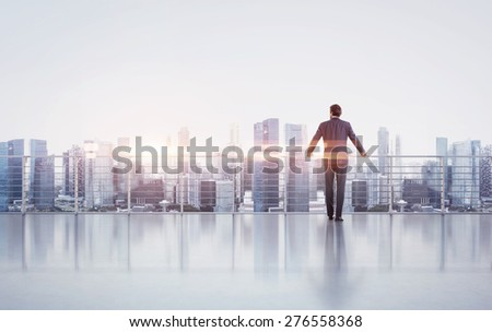 Businessman standing on a roof and looking at sunset
