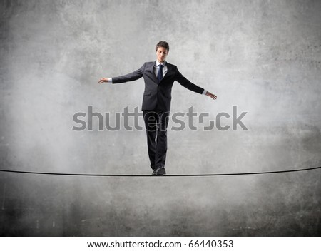 Businessman standing on a rope