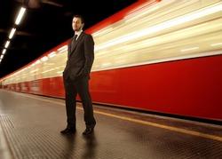 businessman standing on a subway platform