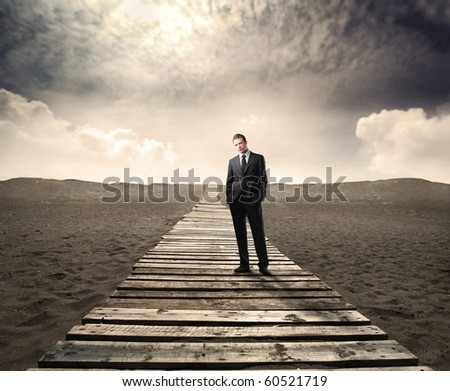 Businessman standing on a wooden path on a desert