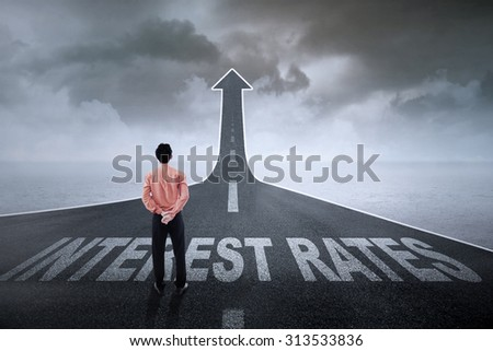 Businessman standing on an asphalt road turning into an ascending arrow with interest rates words on it
