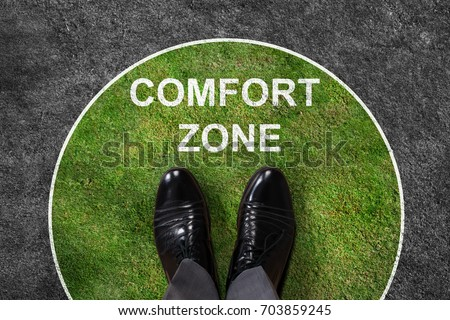 Businessman standing on green and gray carpet with comfort zone text on it #703859245