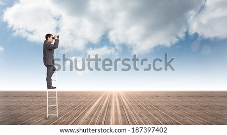 Businessman standing on ladder against cloudy sky background