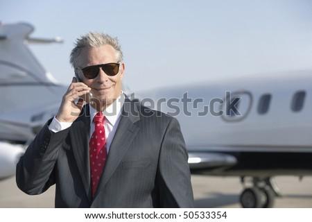Businessman standing on landing strip near private jet, talking on mobile