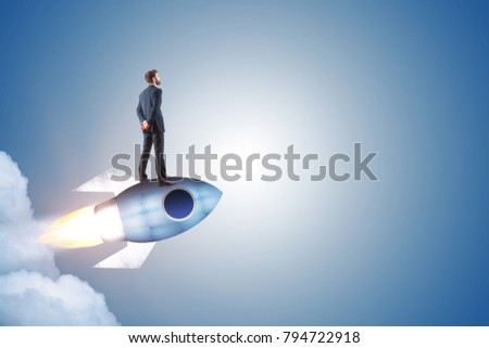 Businessman standing on launching rocket on abstract gray background with copy space. Start up and entrepreneurship concept
