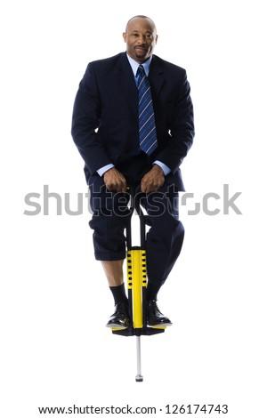 Businessman standing on pogo stick