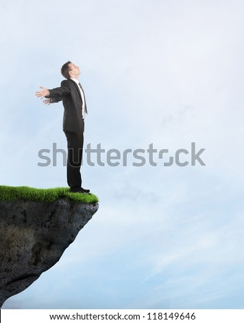 Businessman standing on the cliff