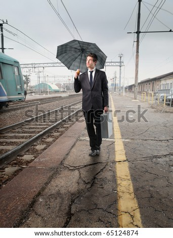 Businessman standing on the platform of a train station