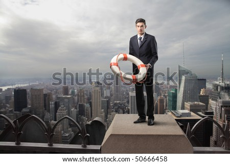 Businessman standing on the top of a skyscraper and holding a lifebelt